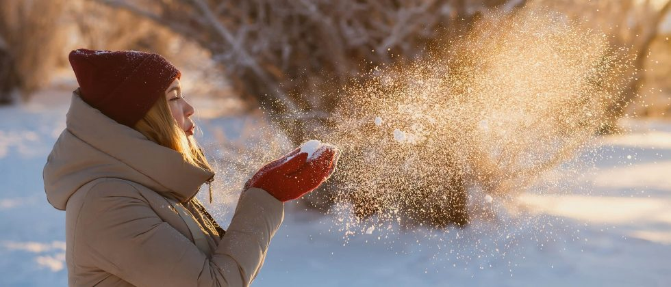 woman in winter blowing snow out of her hands