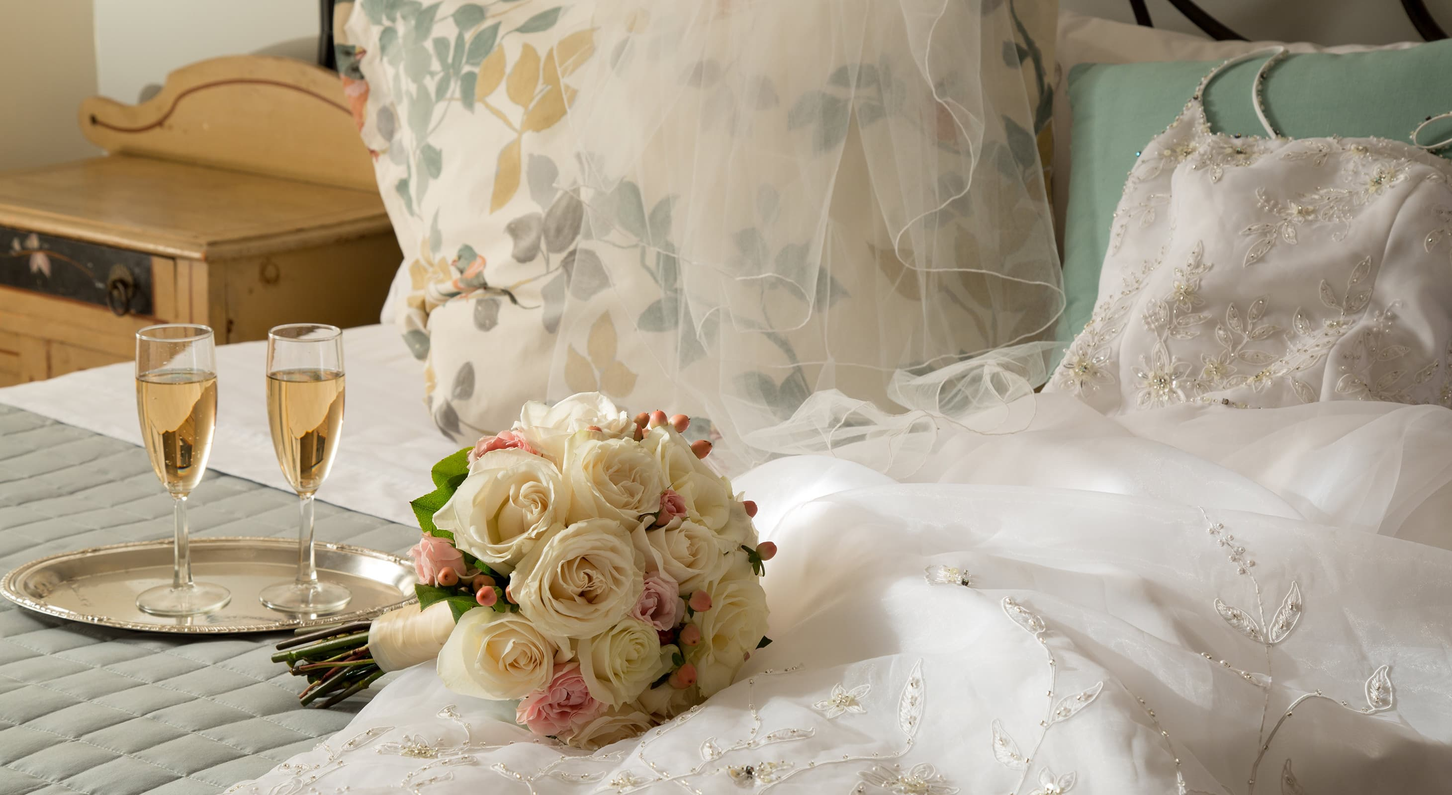 wedding dress, bouquet, and champagne on a bed