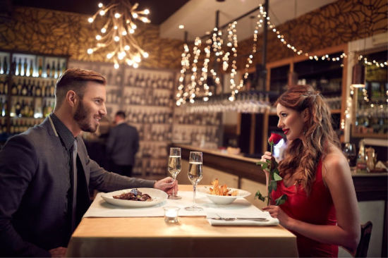 Couple having a romantic dinner with Champagne and a red rose