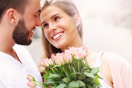Couple smiling holding pink roses