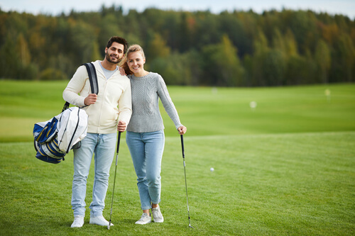 Couple on golf course wearing casual clothes