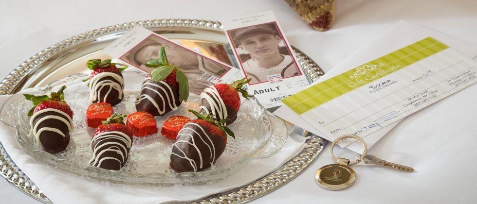 chocolate covered strawberries on a bed with tickets to the Baseball Hall of Fame