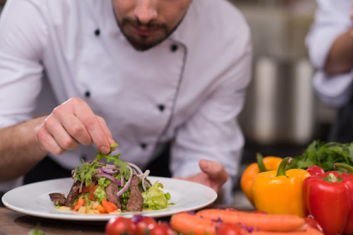 Close up of chef in a white coat adding herbs to a steak salad