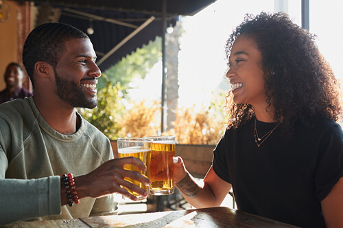 Couple with glasses of beer smiling and doing cheers