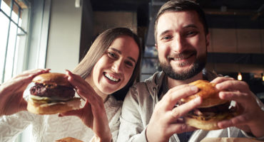 Couple smiling and holding juicy burgers in their hands