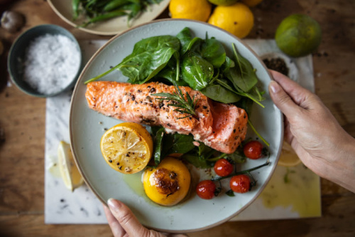 Beautiful plate with salmon spinach and grilled lemons