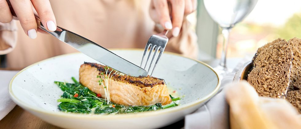 woman cutting a salmon steak at a restaurant