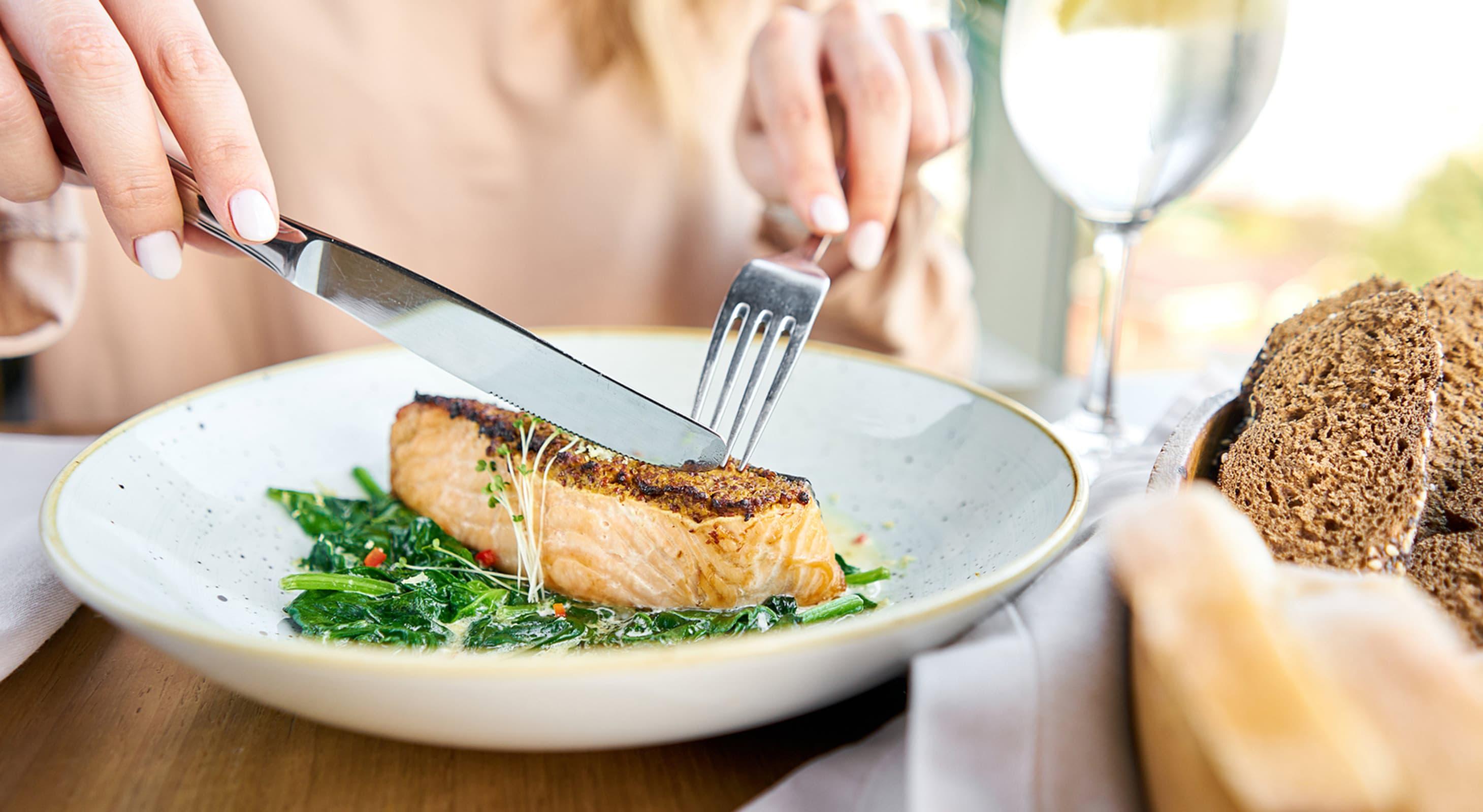 woman cutting a salmon steak at a restaurant