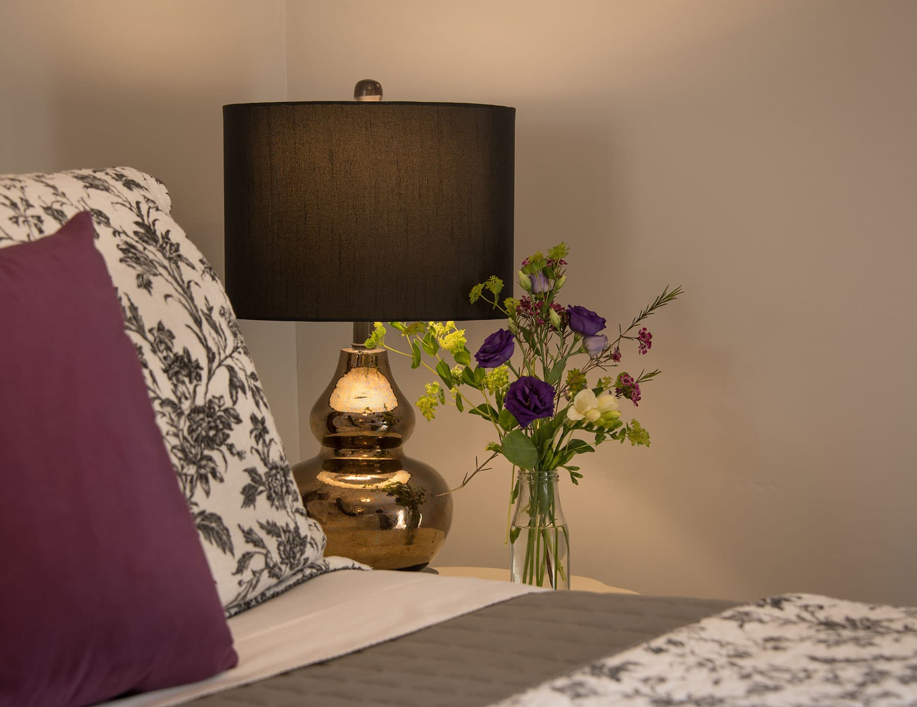 Lamp and purple flower vase on nightstand at a Cooperstown B&B