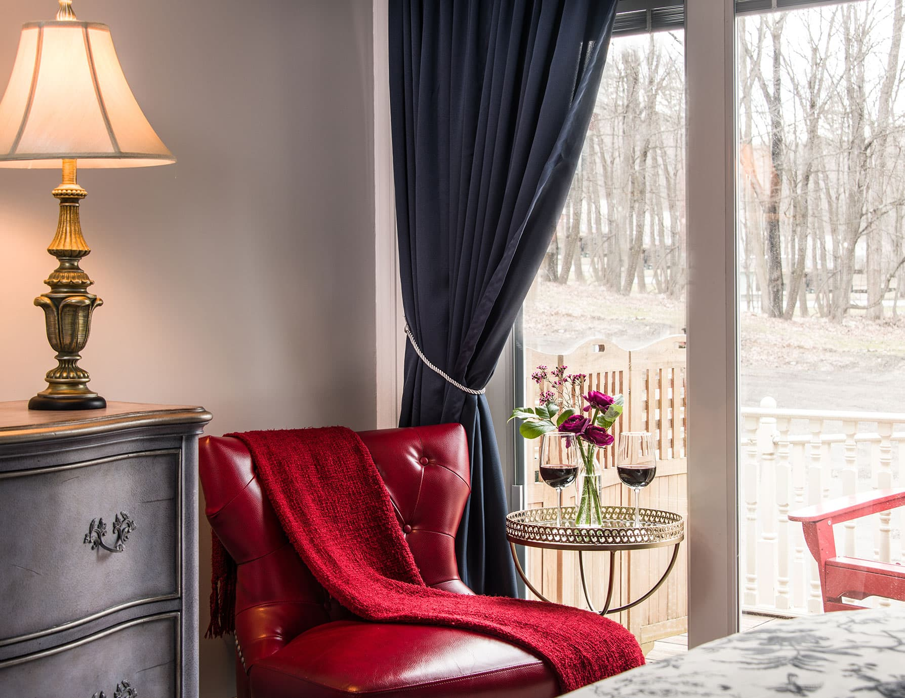 Plush red chair next to table with wine glasses and glass doors looking out on a Cooperstown Bed and Breakfast