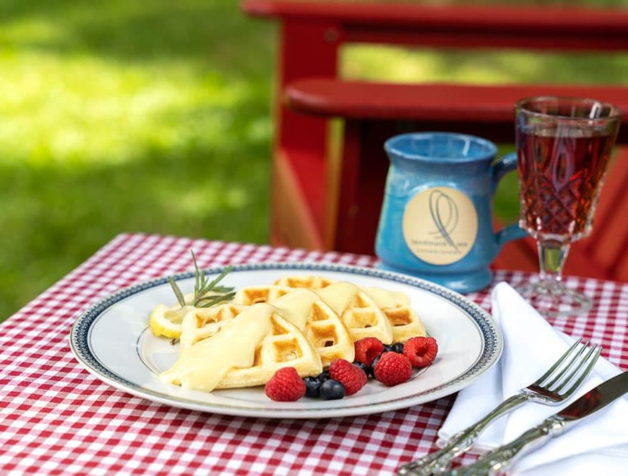 Breakfast waffles on table by Adirondack chairs