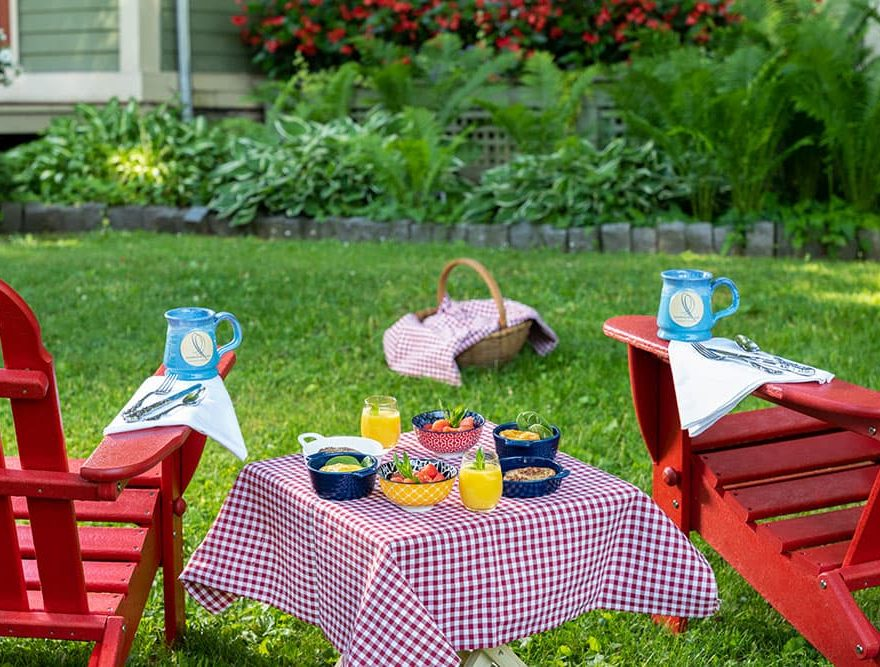 Breakfast waffles on table between Adirondack chairs with signature Landmark Inn mugs