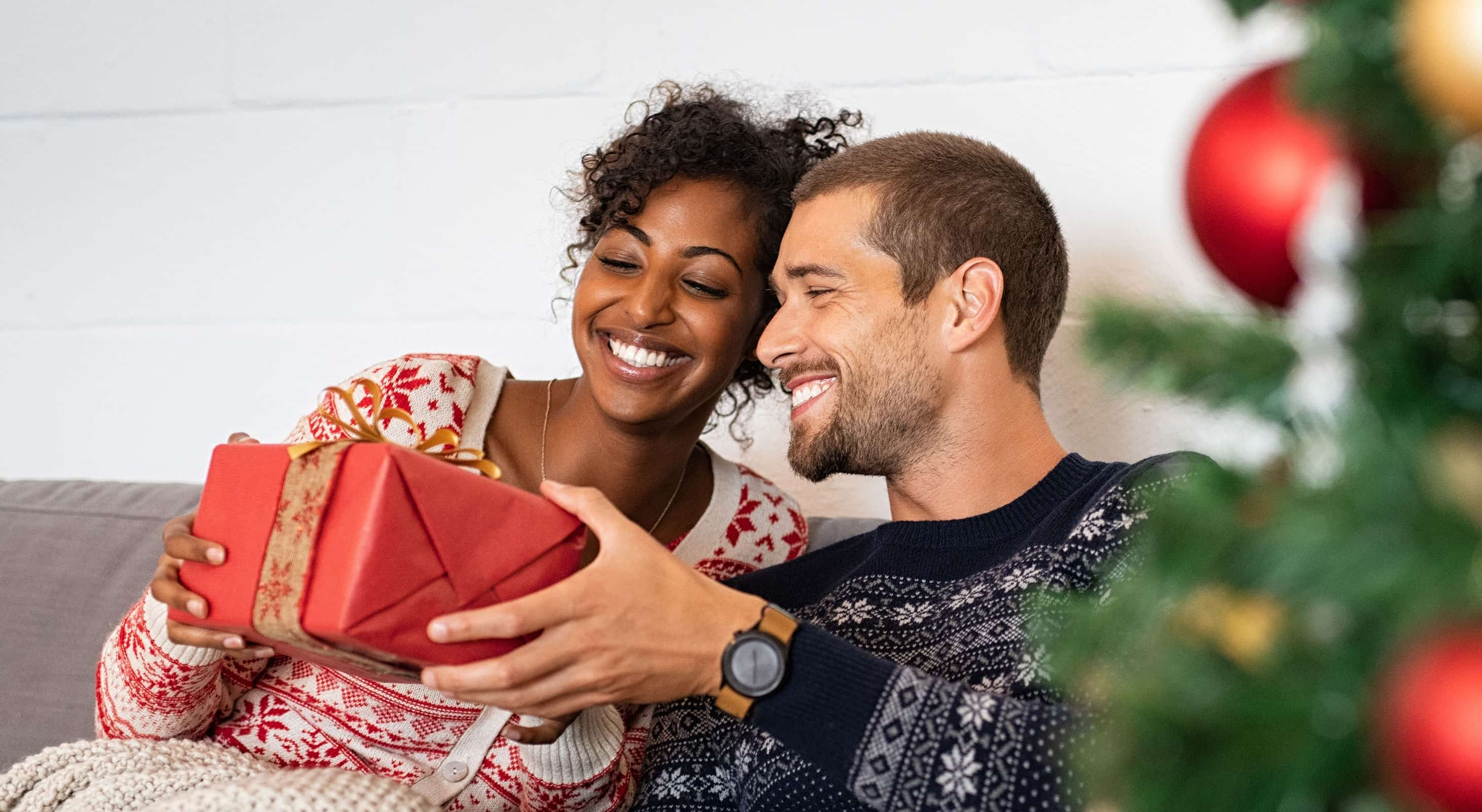 Happy couple opens a Christmas gift together