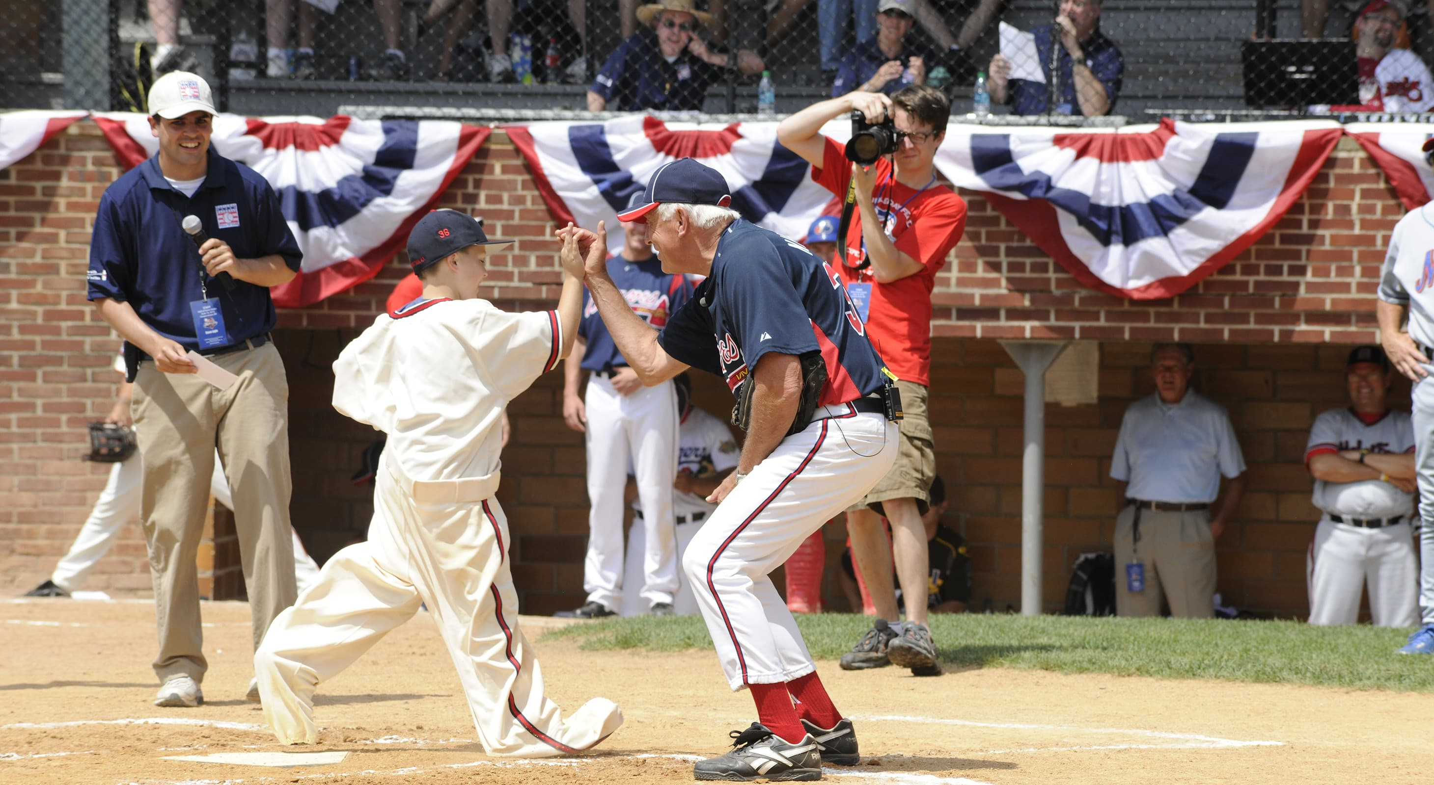 Man high-five a kid running to home plate on a baseball field in Cooperstown, NY