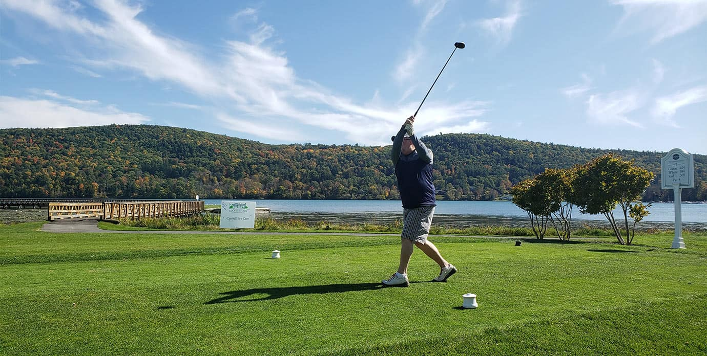 Golfer finishing swing at Leatherstocking Golf Course