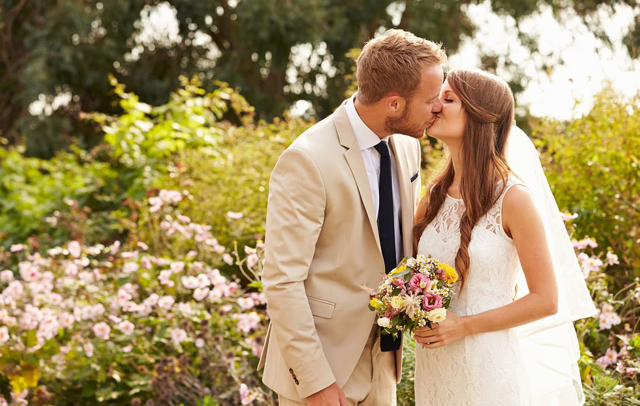 newlyweds kiss in a garden at a Cooperstown Boutique Hotel