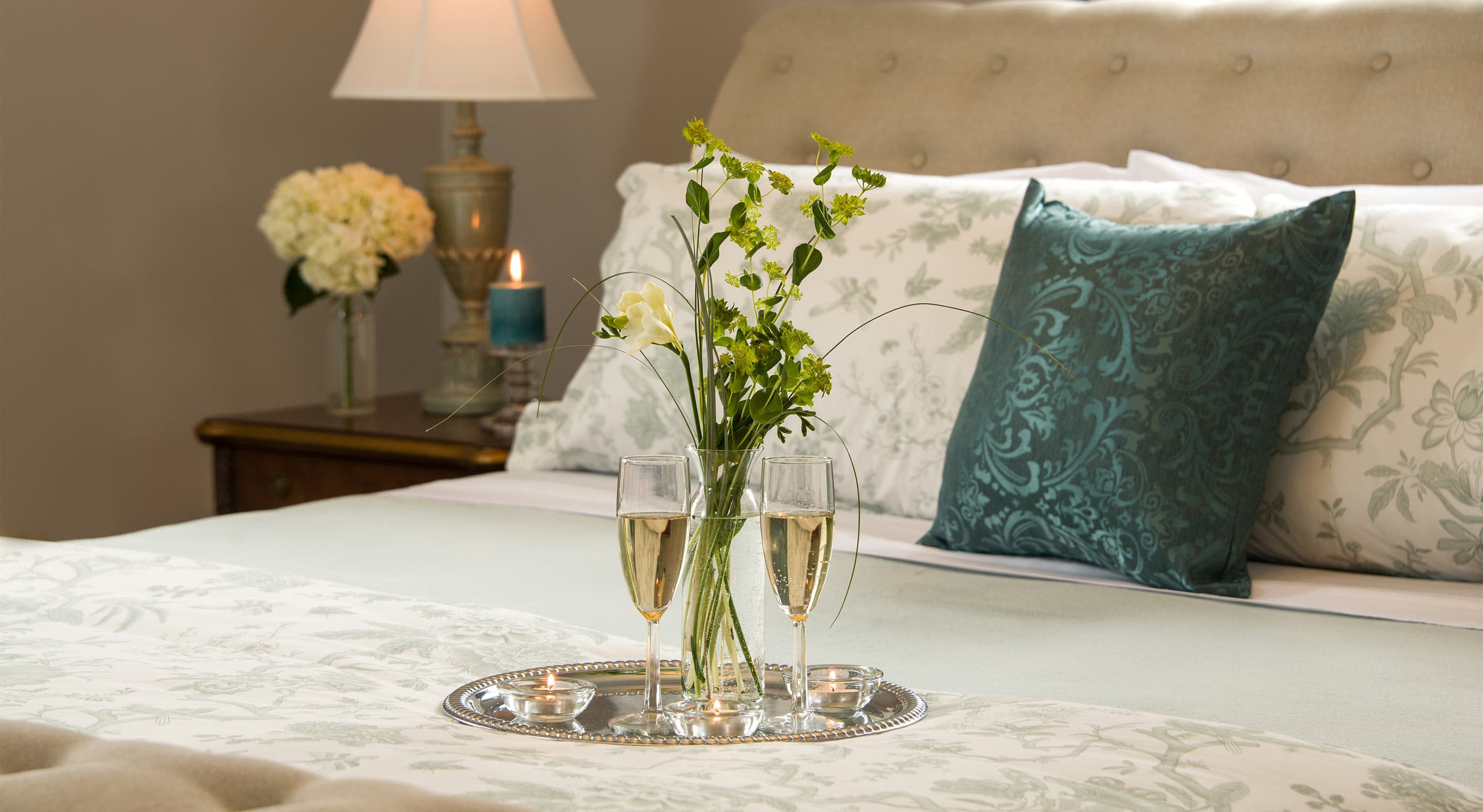 Flowers, champagne, and candles on bed in Summer's Suite