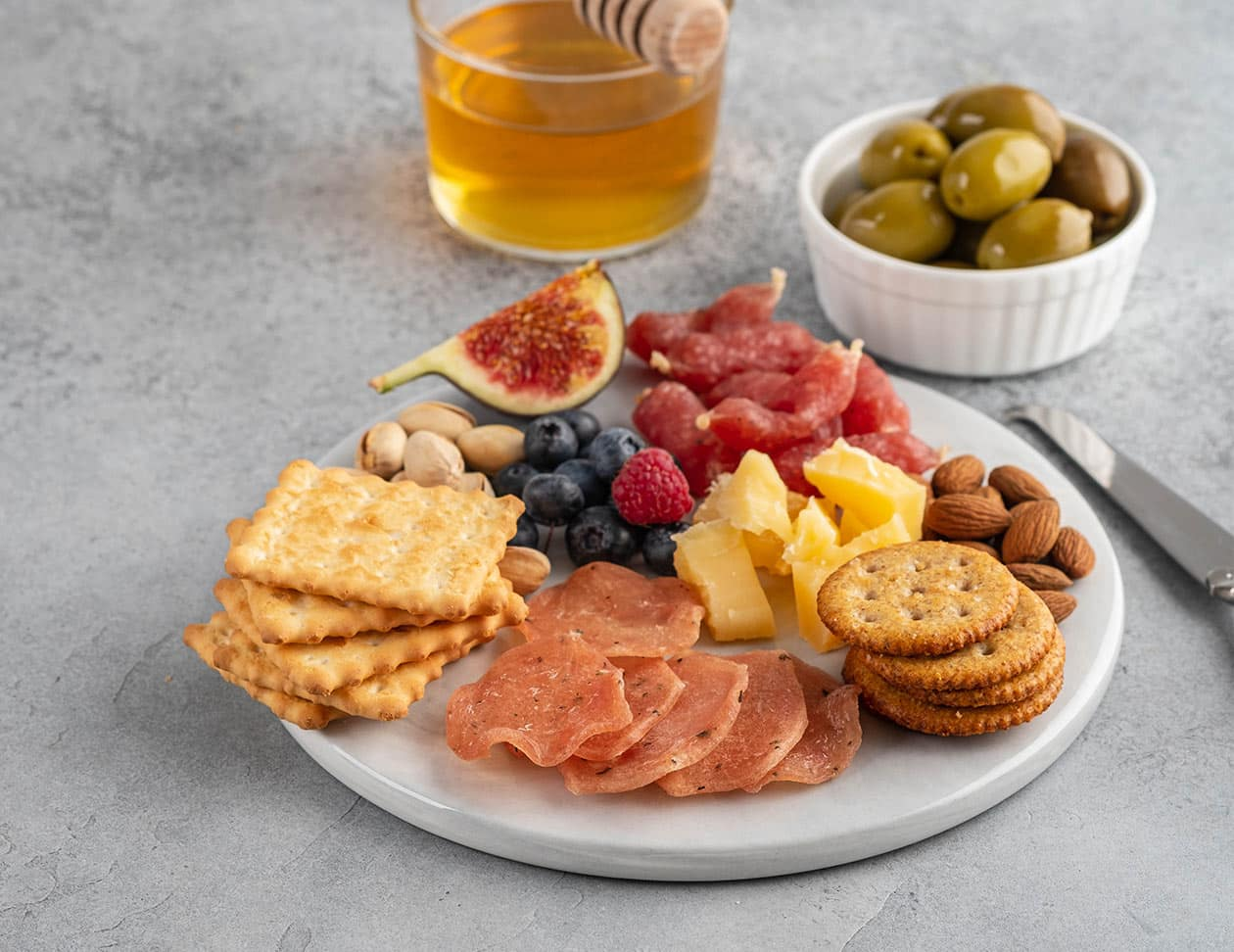 Charcuterie plate with meats, cheese, and olives